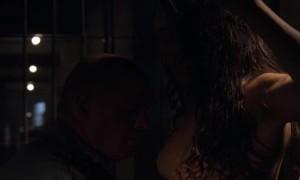 Заключенная показывает свою грудь